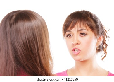 Two young women chatting against white background selective focus