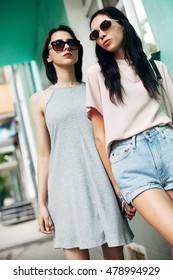 Two young women in the city. Green background