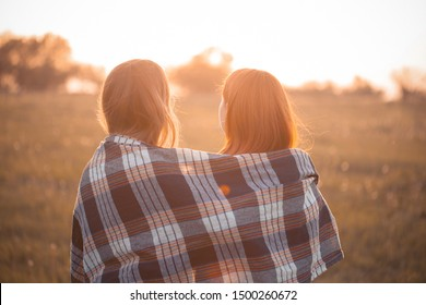Two young women covered by blanket looking on the sunset. Best friends