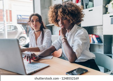 two young women of creative team working indoor using laptop computer - remote working, business, startupper concept