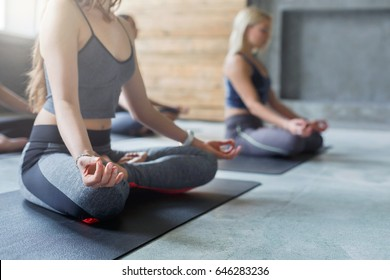 Two young women crop in yoga class making exercises. Unrecognizable girls do meditation pose for relaxation. Healthy lifestyle in fitness club, backlight