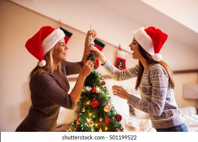 Two young women decorating Christmas tree.
