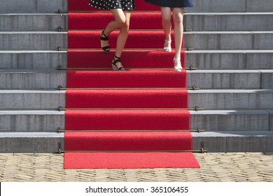 Two young women descending the red carpet staircase