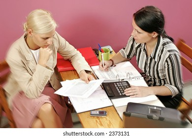 two young women discuss over some paperwork-on pink