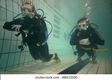 Two young women are diving with equipment in the pool.