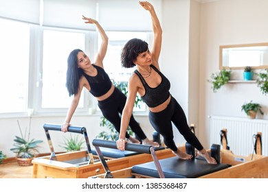 Two Young Women Doing  Exercises on Pilates Bed  at  Gym