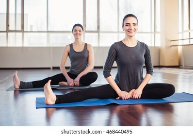 Two young women doing stretching out in the fitness room