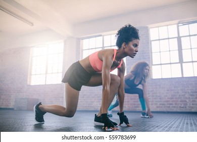 Two young women doing workout together in gym. Females doing running exercise in fitness class.