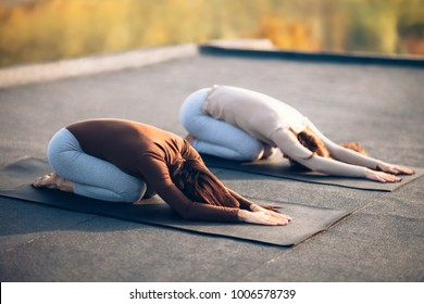 Two young women doing yoga asana child's pose on the roof outdoor. Utthita Balasana