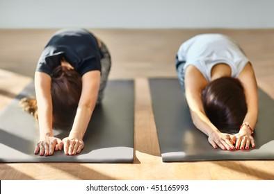 Two young women doing yoga asana Child's Pose. Utthita Balasana