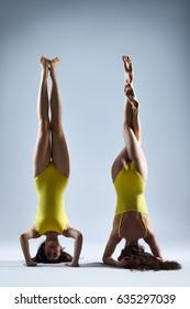 Two young women doing yoga asana supported headstand. Salamba Sirsasana