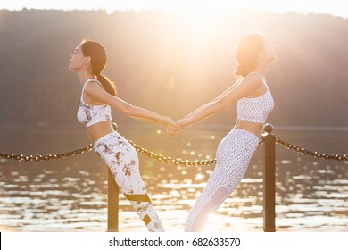 Two young women doing yoga at nature. Fitness, sport, yoga and healthy lifestyle concept - group of people making yoga pose on lake pier at sunset