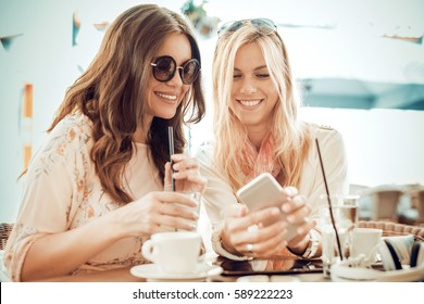 Two young women drinking coffee and using phone in cafe.