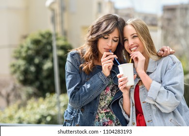 Two young women drinking the same take away glass together with two straws outdoors.