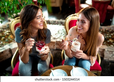 Two young women eating ice cream from cups in a sweet house