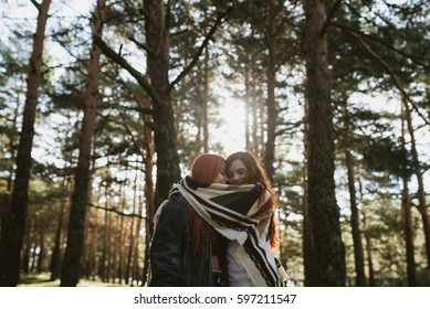 Two young women embracing under the plaid in sunny forest.