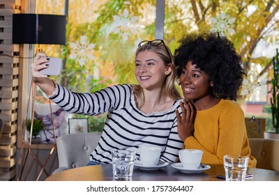 Two young women enjoying coffee together in a coffee shop, sitting at table taking a selfie with a smartphone.  Diversity and multi ethnic concept. No to racism.