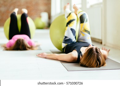 Two young women exercising with fitness balls at a bright fitness studio