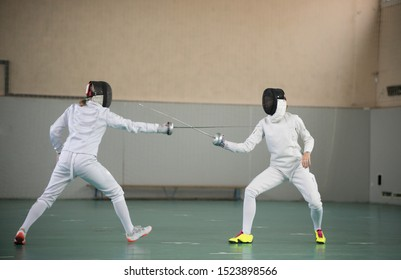 Two young women fencers having a training at the gym