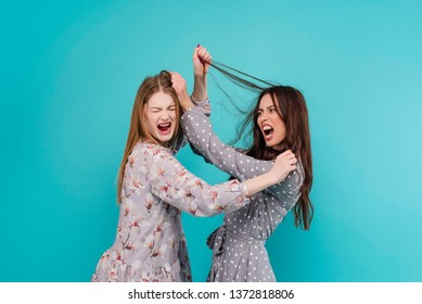 two young women fighting and pulling hair isolated over turquoise blue background