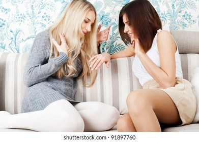 Two young women friends chatting at home. One showing to another her proposal ring