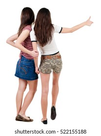 Two young  women friends showing thumbs up.  backside view of person. Isolated over white background. Rear view people collection.