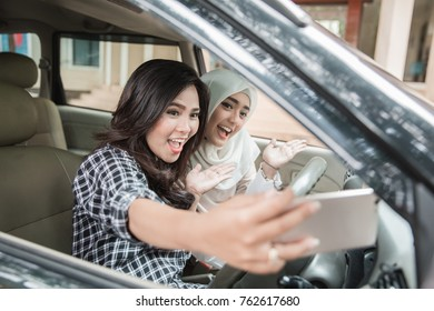 Two young women hangout on car trip.They are driving the car and taking selfie