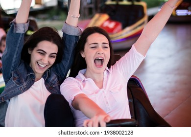Two young women having a fun bumper car ride at the amusement park in the summer.