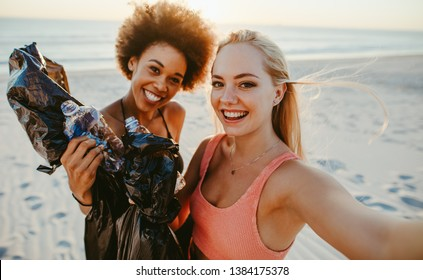 Two young women holding garbage bags and taking selfie at the beach area. Two girls cleaning up rubbish on beach and taking a selfie.