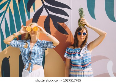 Two young women holding oranges and a pineapple on the beach