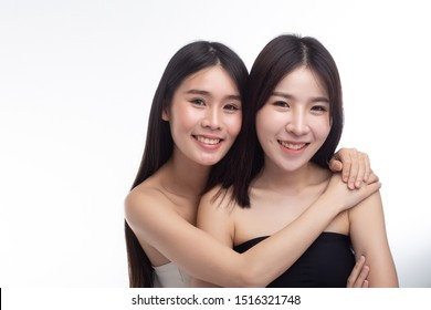 Two young women hug each other happily.