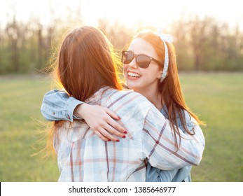 Two young women hugging outdoors at sunset. Best friends