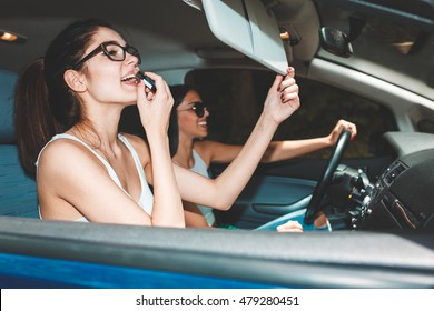 Two young women inside the car.They are driving the car and fixing makeup.Preparing to go out.Clubbing and nightlife.