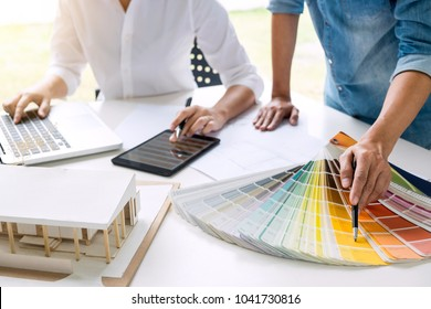 Two young women interior design or graphic designer working on project of architecture drawing with work tools and color swatches, colour chart in digital tablet at workplace.