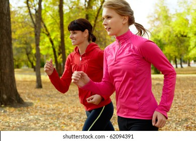 Two young women jogging in autumn park