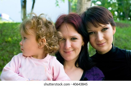 Two young women with a little child on hands against summer nature. Shallow DOF