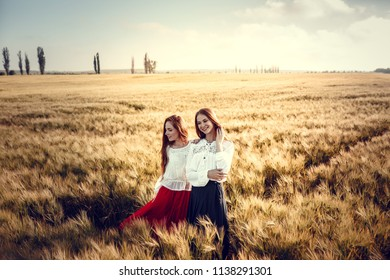 Two young women are looking forward tothe sunset. Best friends. Two young red-haired women in a wheat field
