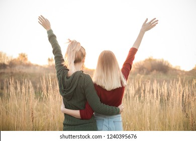 Two young women are looking on the sunset and rise up hands. Best friends