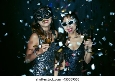 Two young women in masks dancing at the party