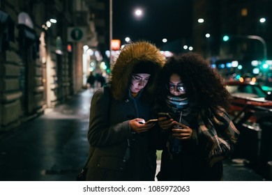 two young women multiethnic outdoor using smart phone outdoor at night - phubbing, social network, communication concept