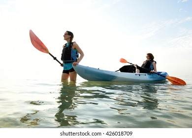 Two young women in ocean with a kayak