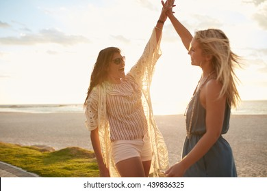 Two young women on the beach giving high five. Women friends enjoying beach vacation.
