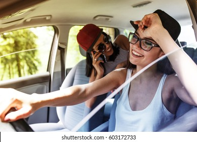 Two young women on car trip having fun