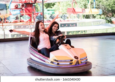 Two young women on a fun bumper car ride together at the amusement park in the summer.