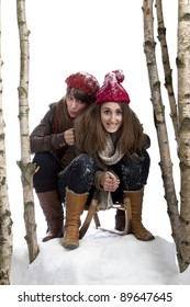 two young women on a sledge between birch trees