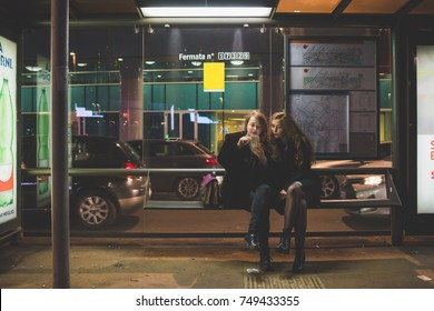two young women outdoor bus stop using smart phone - internet, social network, technology concept