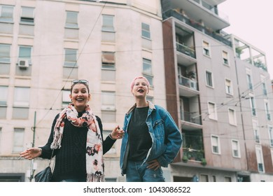 two young women outdoors having fun - best friends, bonding, interaction concept