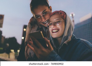 two young women outdoors in the night using smart phone face illuminated screen light - online, youth culture, internet concept