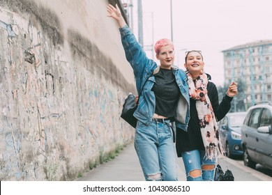 two young women outdoors walking hugging - best friends, bonding, interaction concept