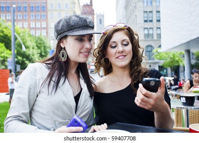 two young women outside at a cafe reading text message